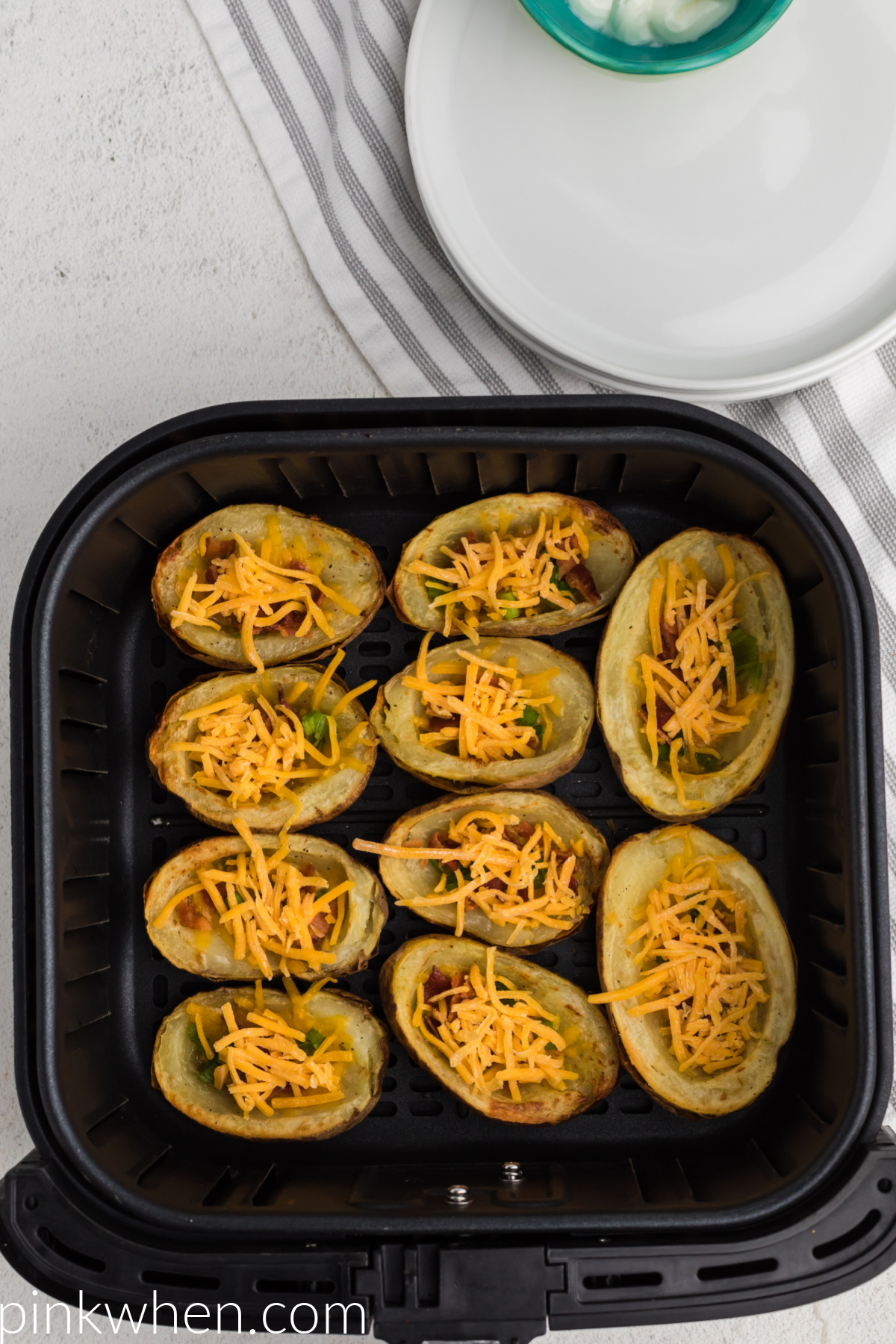 Potato skins loaded with cheese, bacon, and green onion tops ready to be cooked in the air fryer.