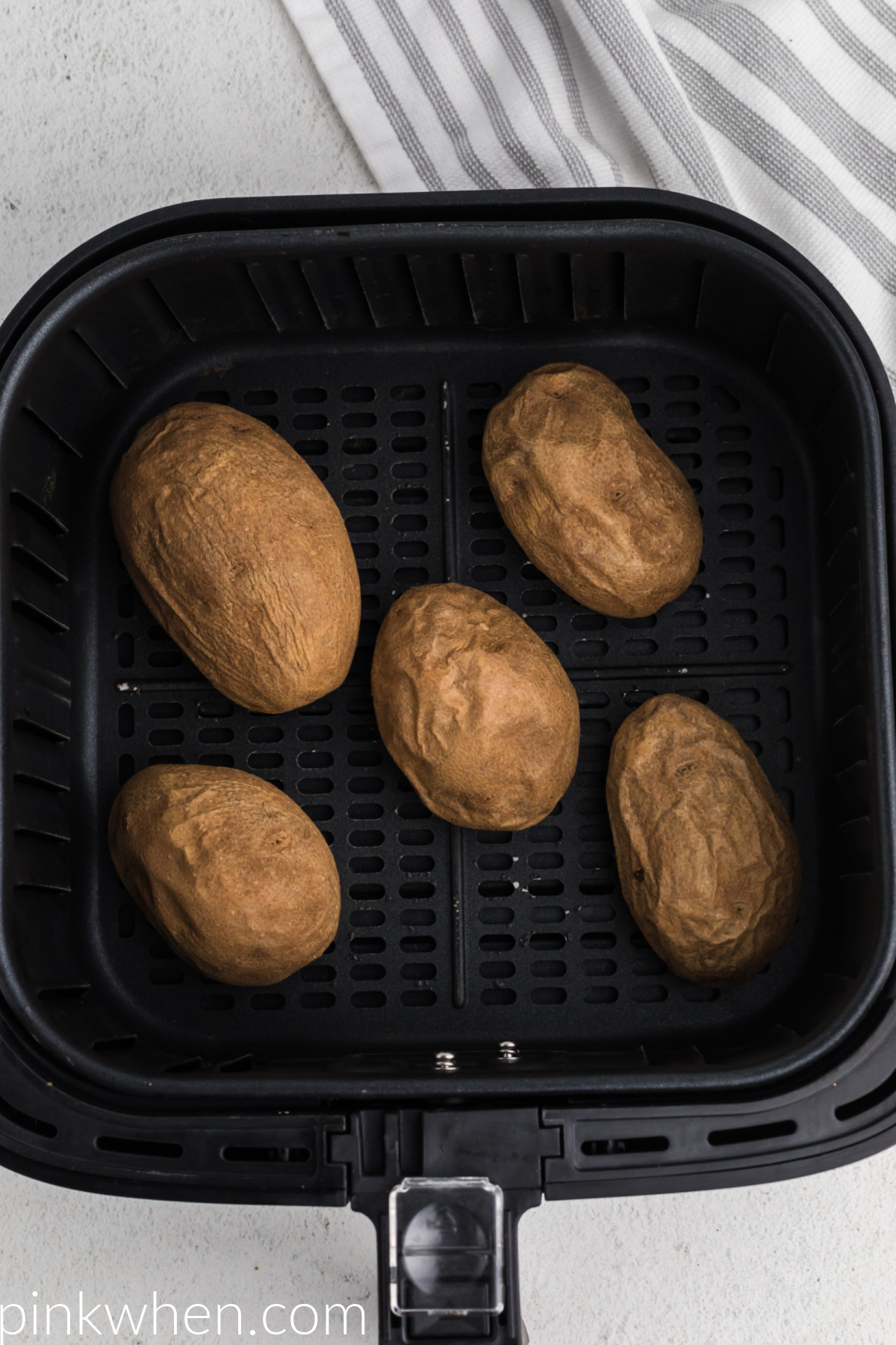 Cooked potatoes in the basket of the air fryer