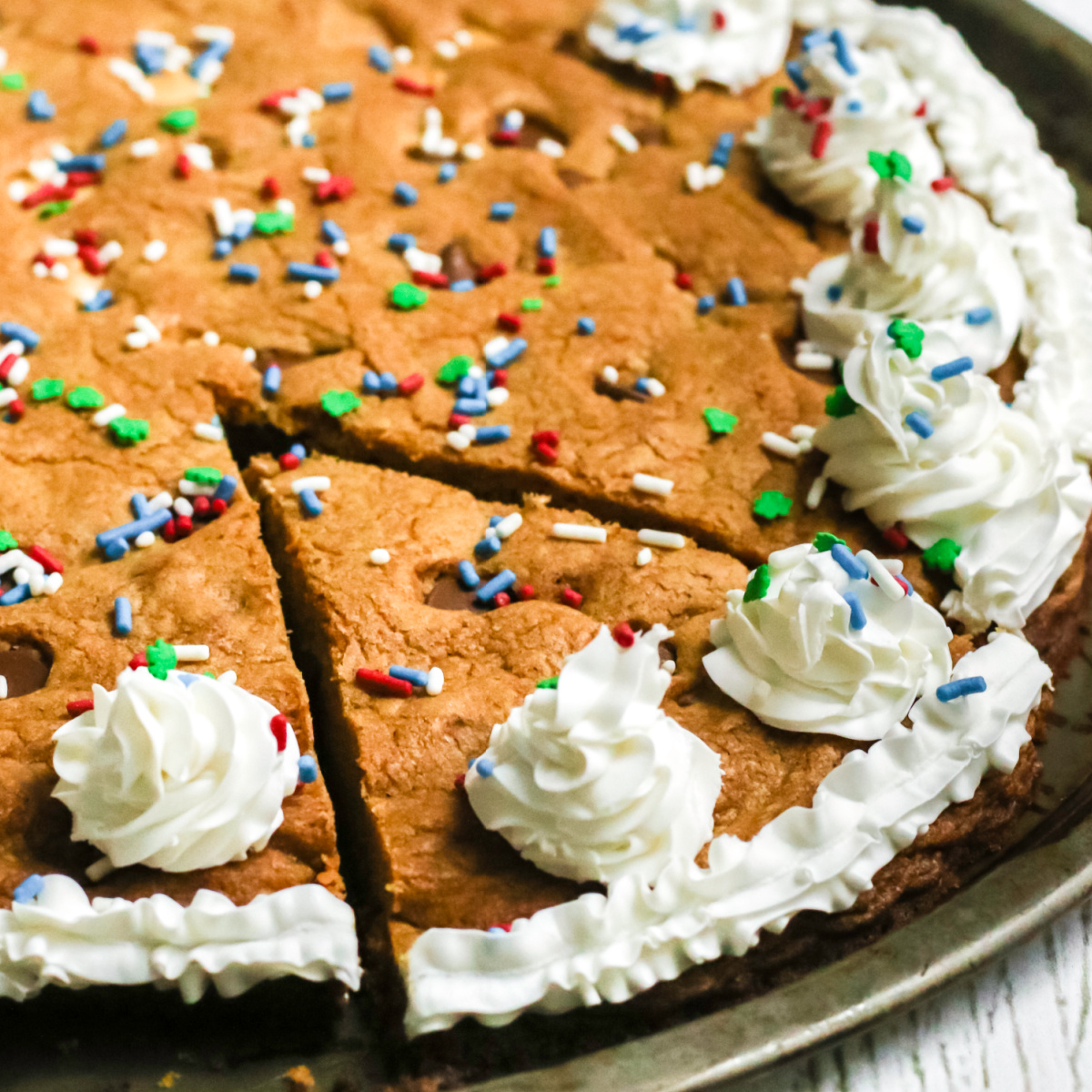 chocolate chip cookie cake on a pan with a slice cut and ready to serve.