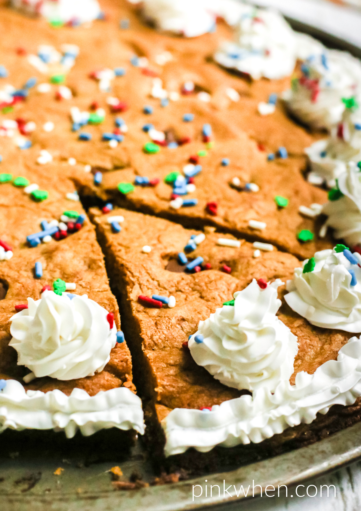 Homemade chocolate chip cookie cake on a pan and topped with frosting and sprinkles and ready to serve.