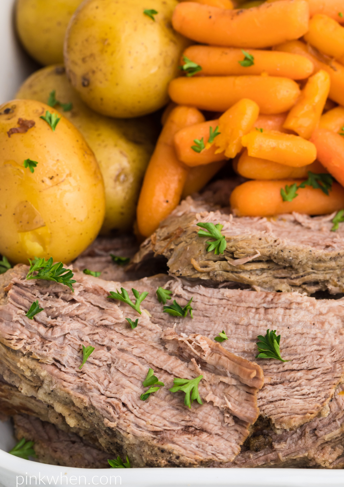 Instant Pot Tri Tip roast sliced and served with vegetables and garnished with fresh parsley.