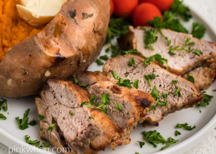Air Fried Pork Tenderloin on a ehite plate with a sweet potato and tomatoes and garnished with fresh parsley.