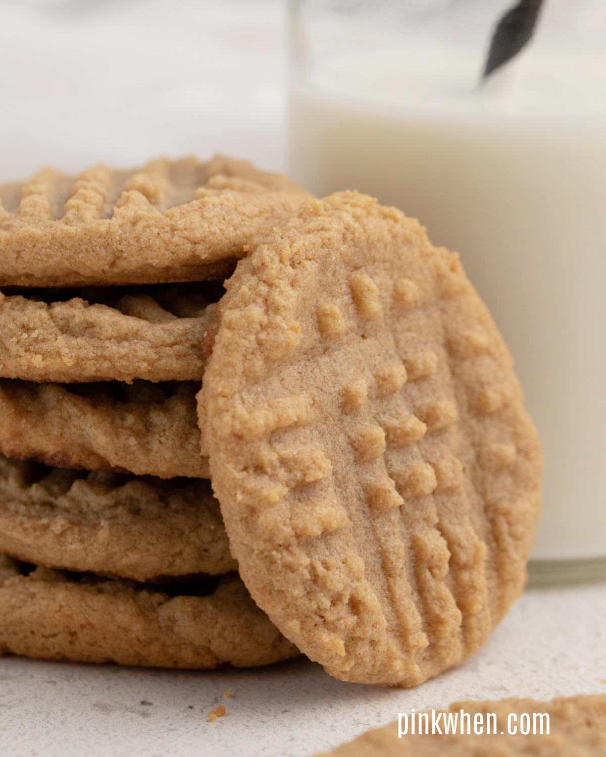 Close up photo of peanut butter cookies stacked next to a glass of milk.