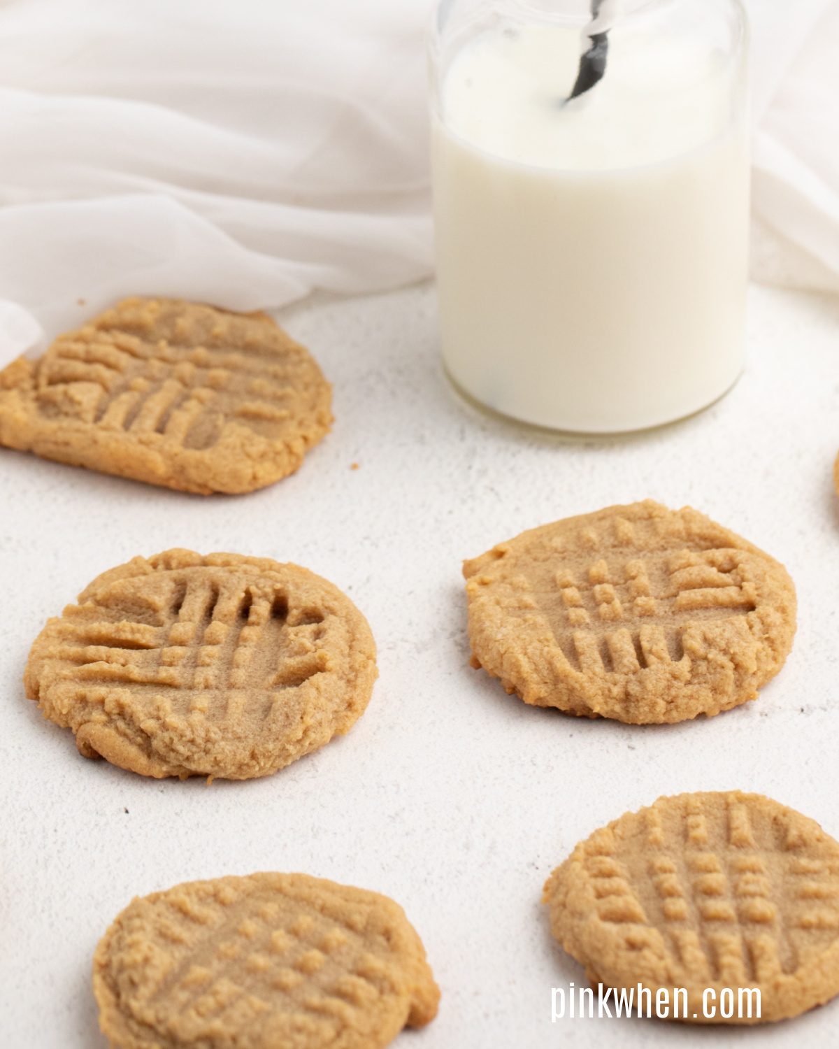 Peanut butter cookies laid out on a table with a glass of milk.