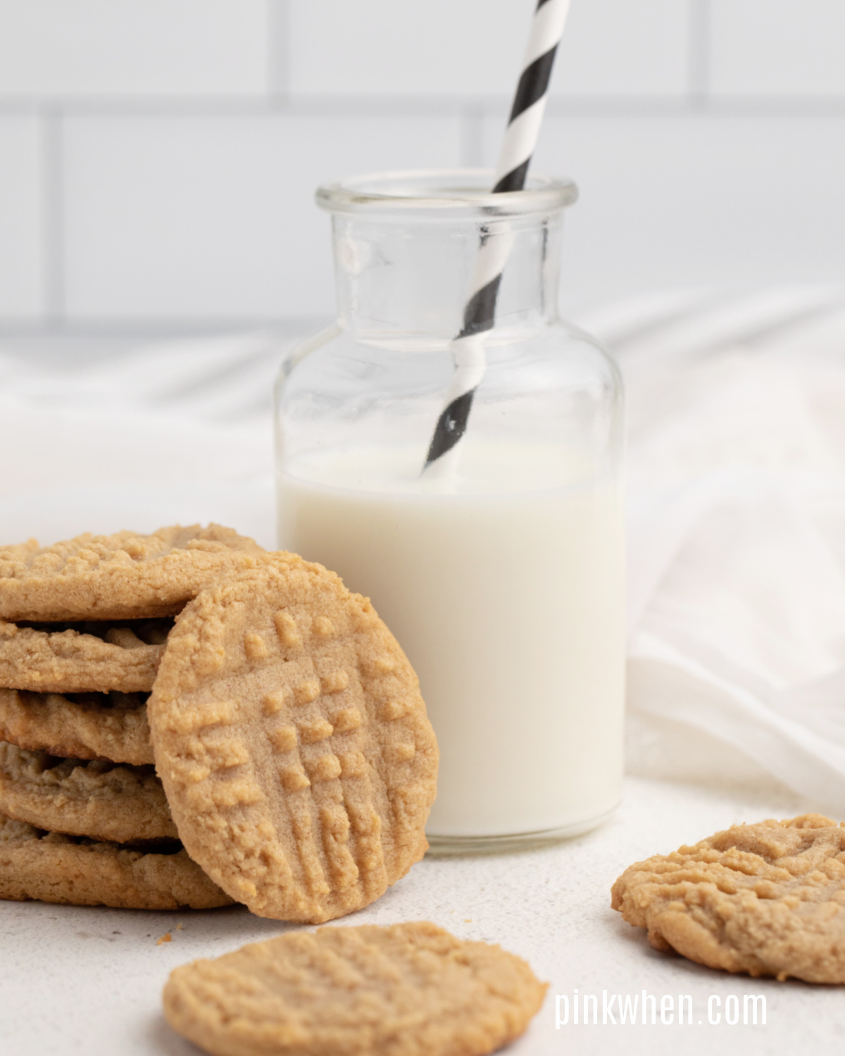 3 Ingredient Peanut Butter Cookies on a white table with a glass of milk.