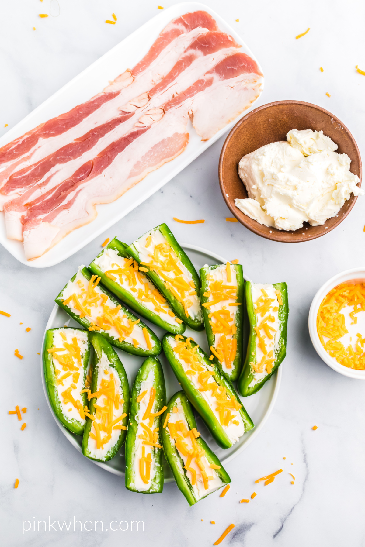 Jalapeno peppers cut lengthwise and stuffed with cream cheese and topped with cheddar cheese.