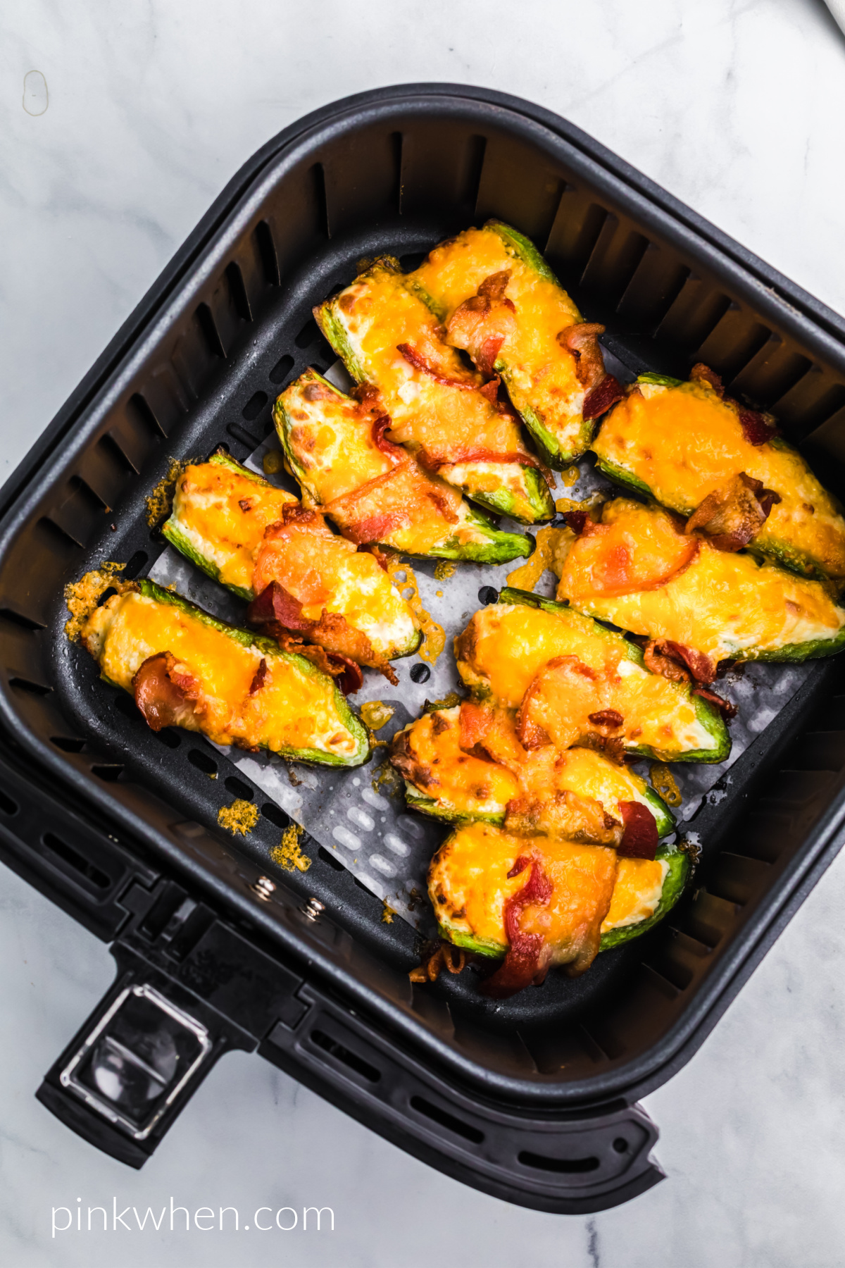 air fried jalapeno poppers in the basket of the air fryer.
