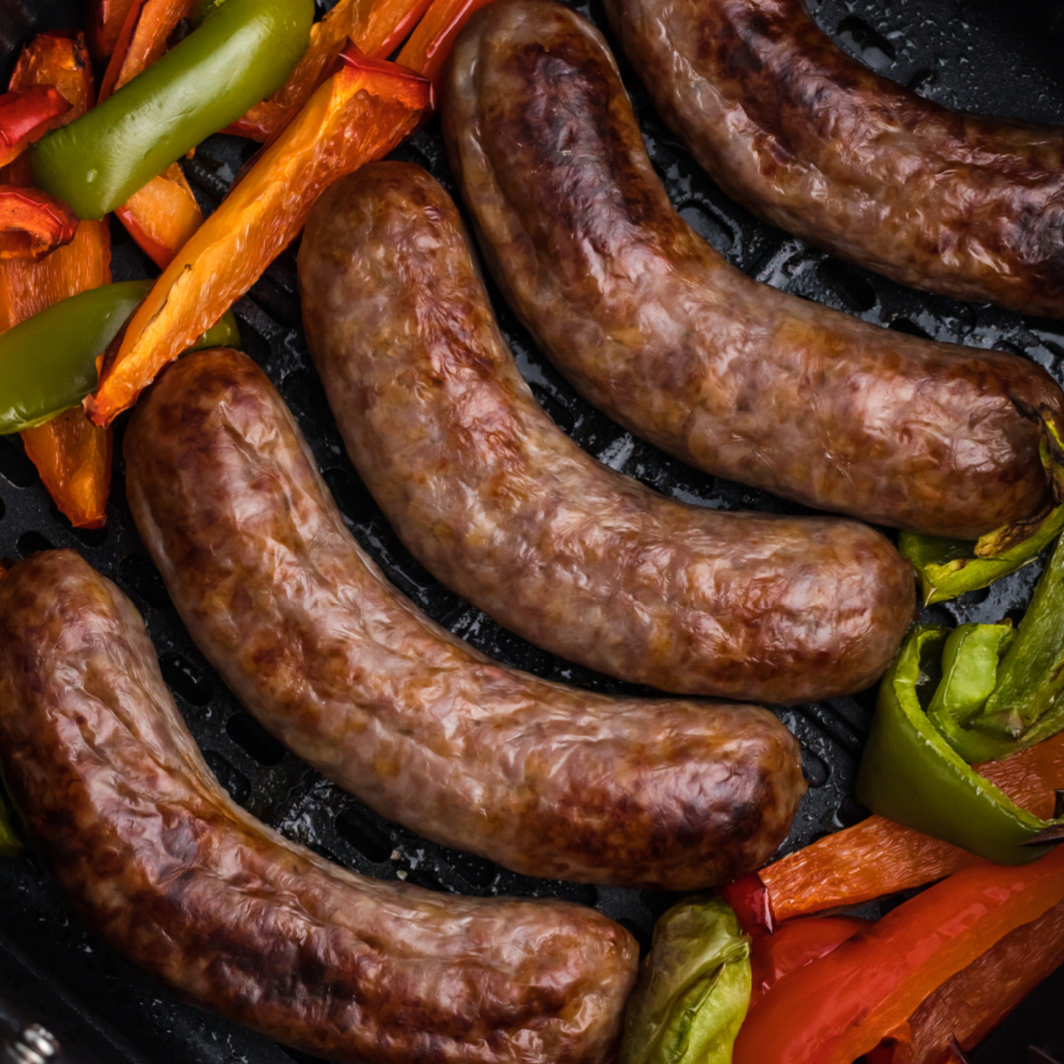 brats and bell peppers fully cooked in the basket of the air fryer.