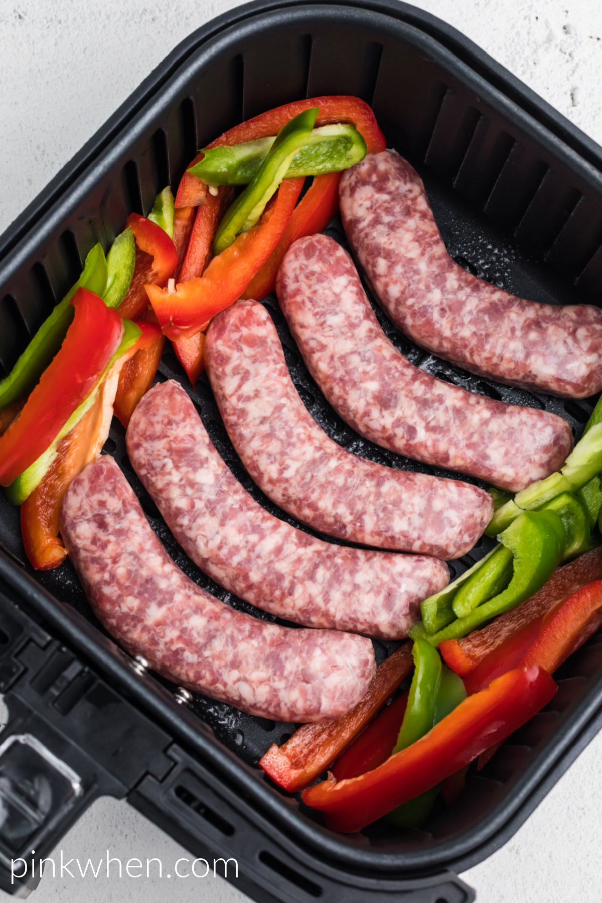 bell peppers and brats in the air fryer basket, ready to cook.
