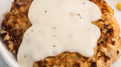 Air Fried Chicken Fried Steak topped with white gravy on a white plate ready to serve.