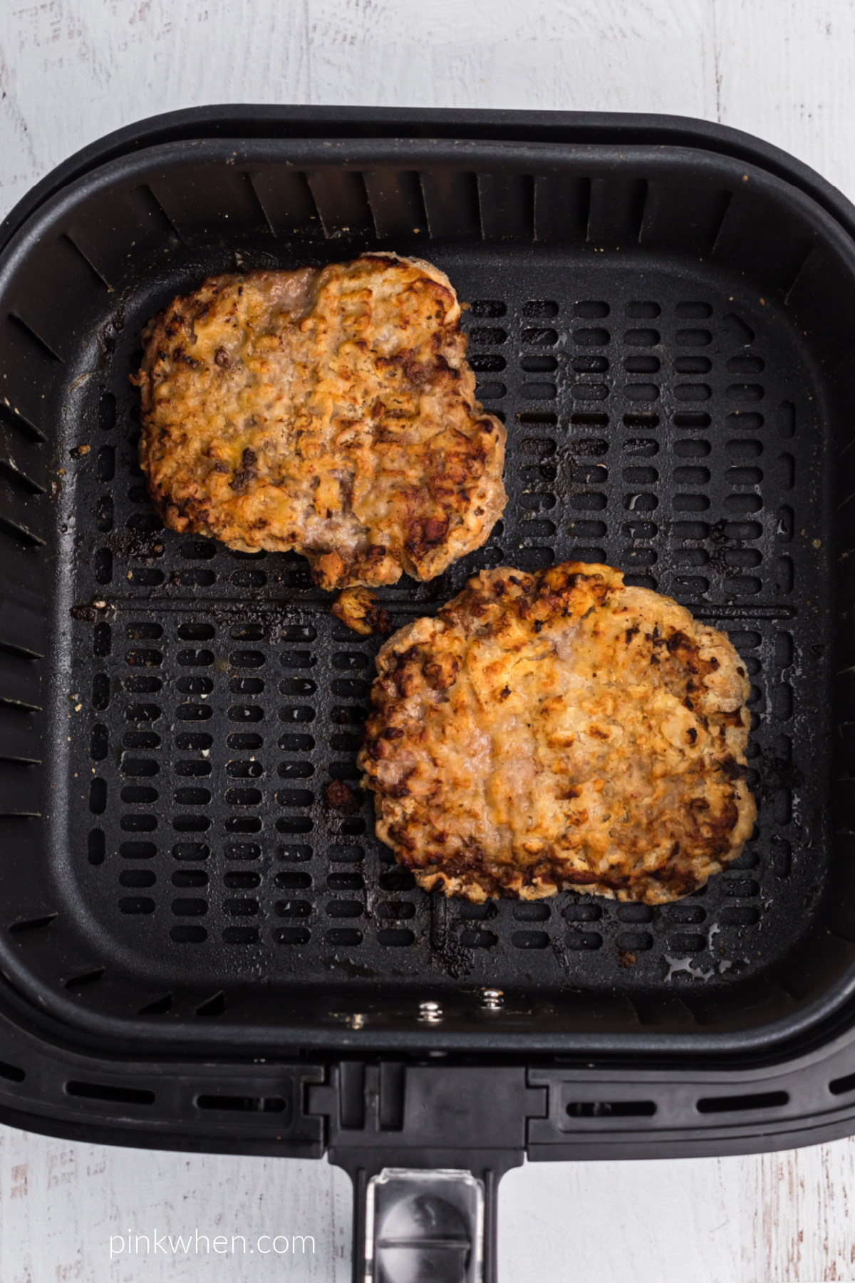 Chicken Fried Steaks fully cooked in the basket of the air fryer.