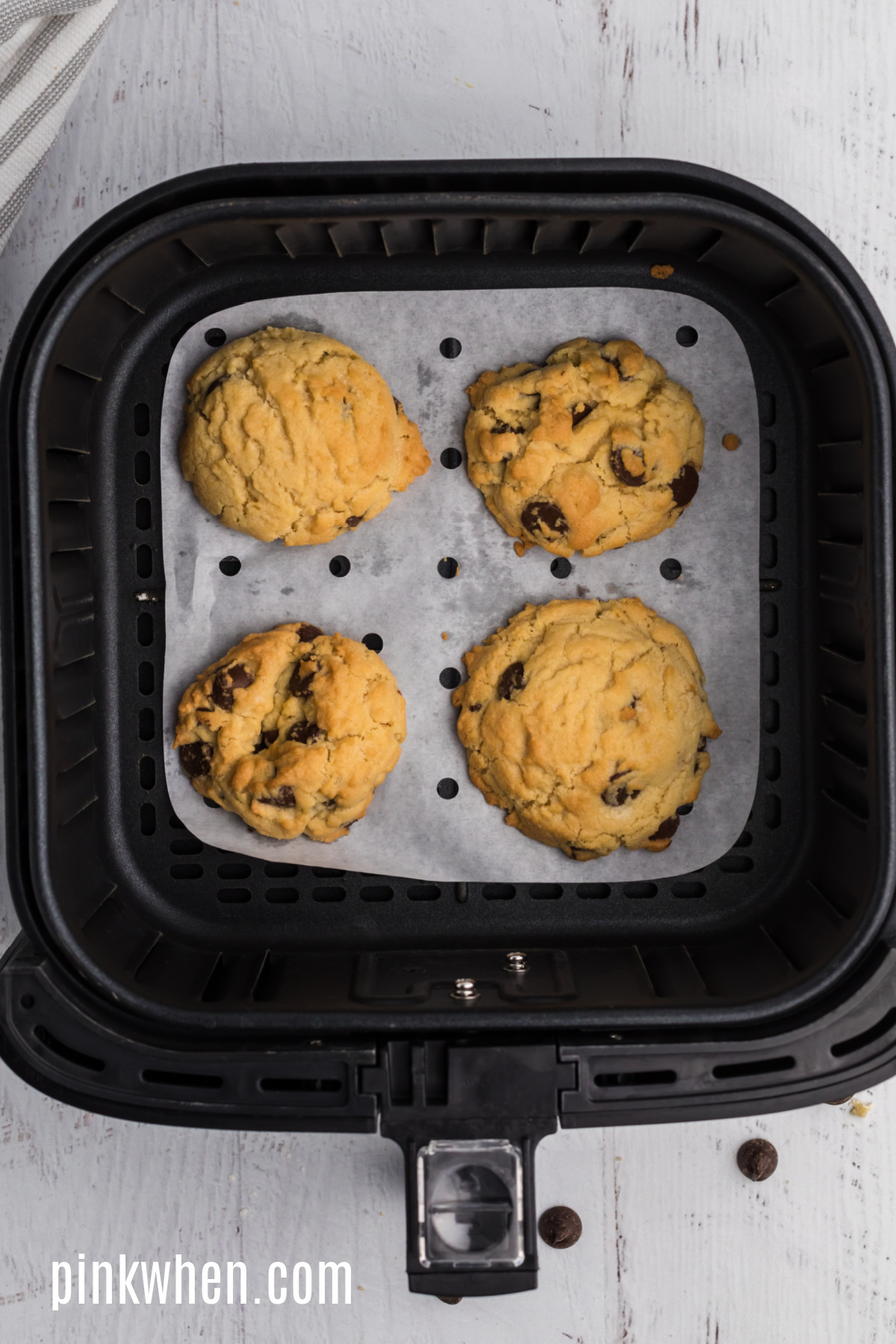 Larger sized Chocolate chip cookies in the basket of the air fryer.