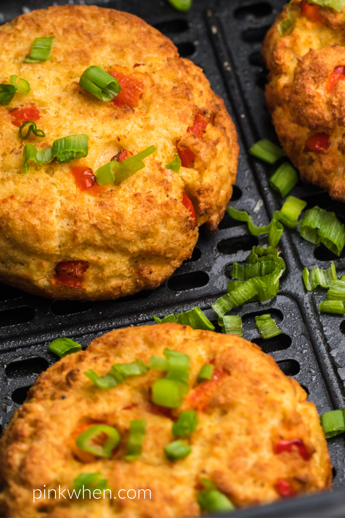 Close up photo of cooked crab cakes in the air fryer basket.