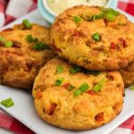 Crab cakes on a plate topped with fresh green onion tops.