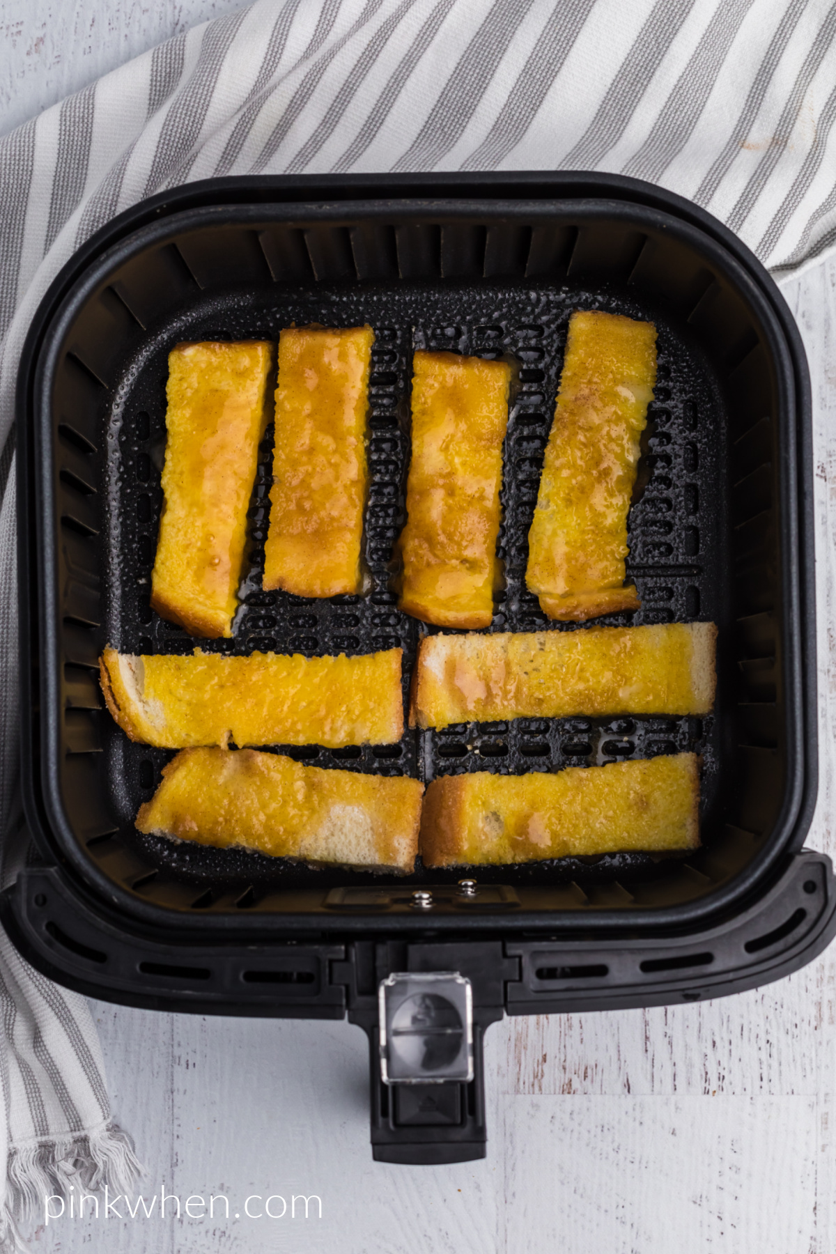 French toast sticks in the basket of the air fryer ready to be cooked.
