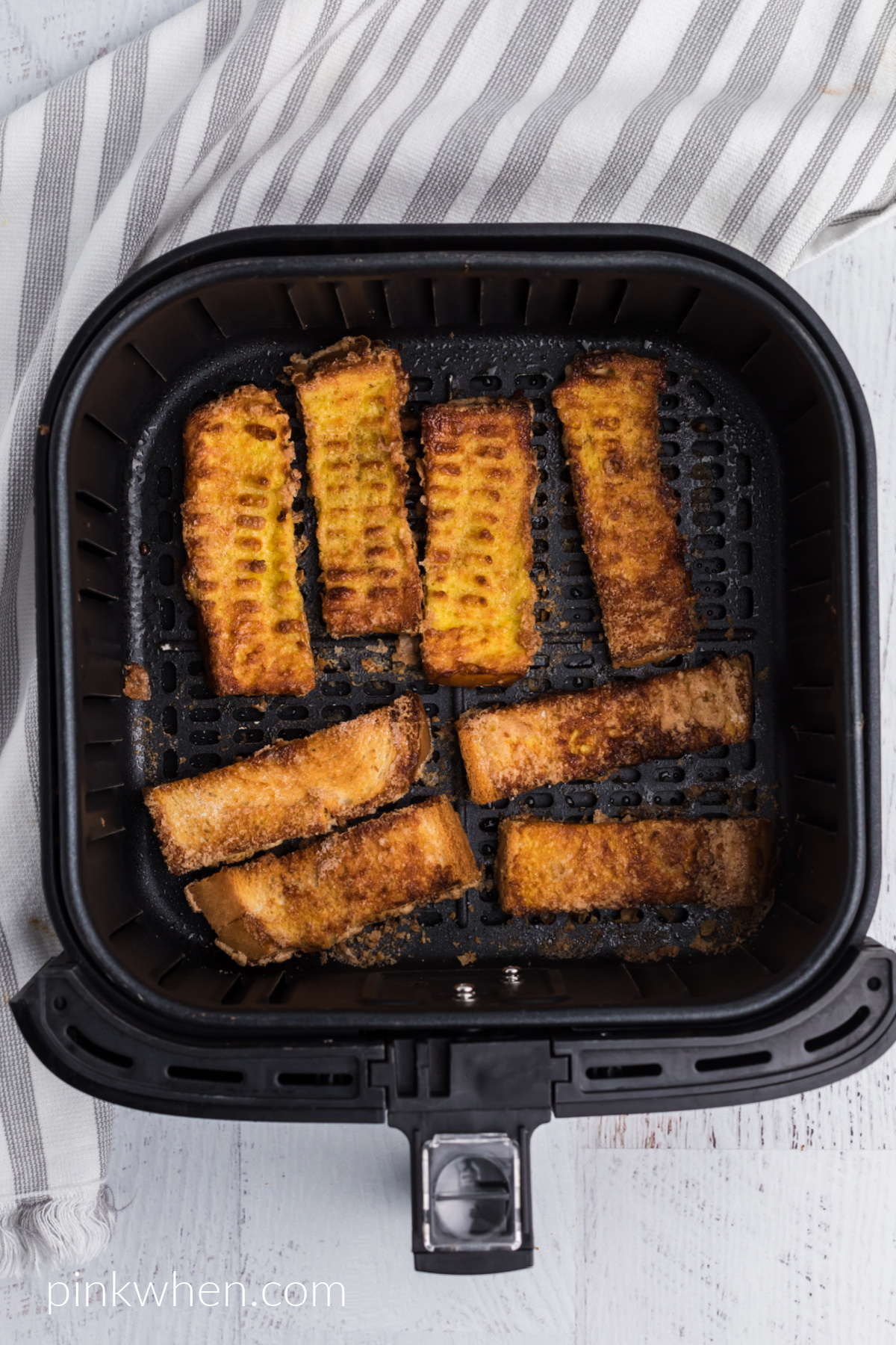 cooked french toast sticks in the air fryer basket.