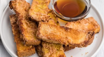 French toast sticks on a white plate with syrup for dipping sauce, ready to eat.