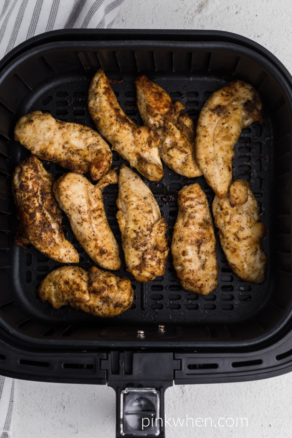 Grilled chicken tenders in the basket of the air fryer.