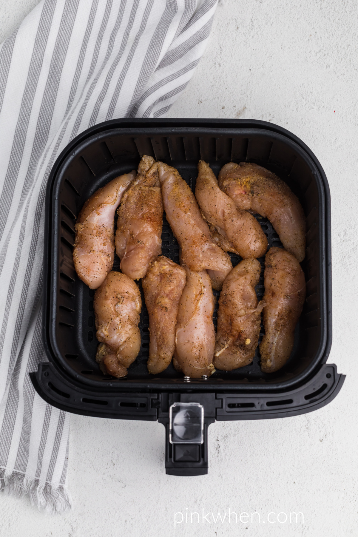 chicken tenders in the air fryer basket ready to be cooked.