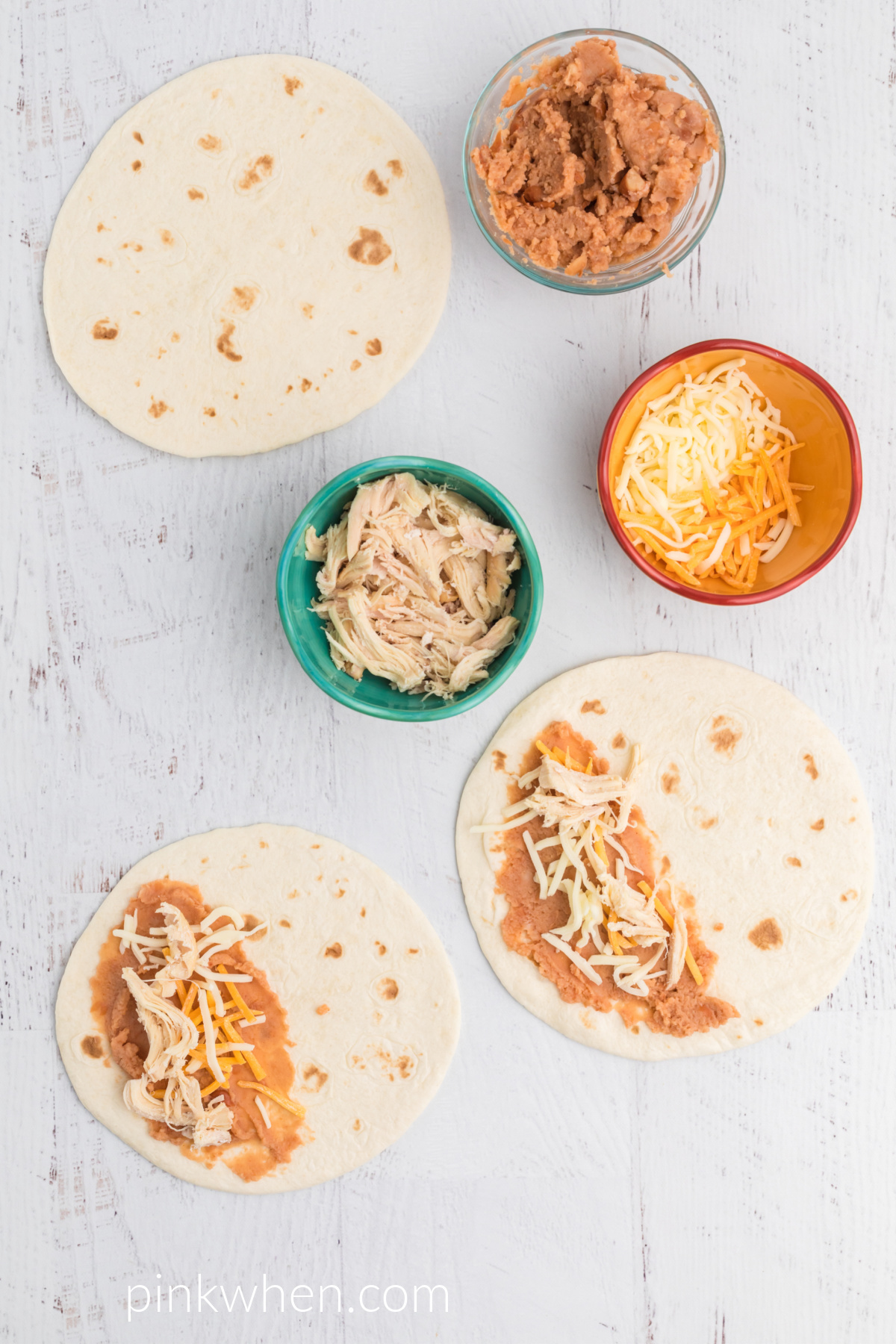 Tortillas with refried beans and shredded cheese on top.