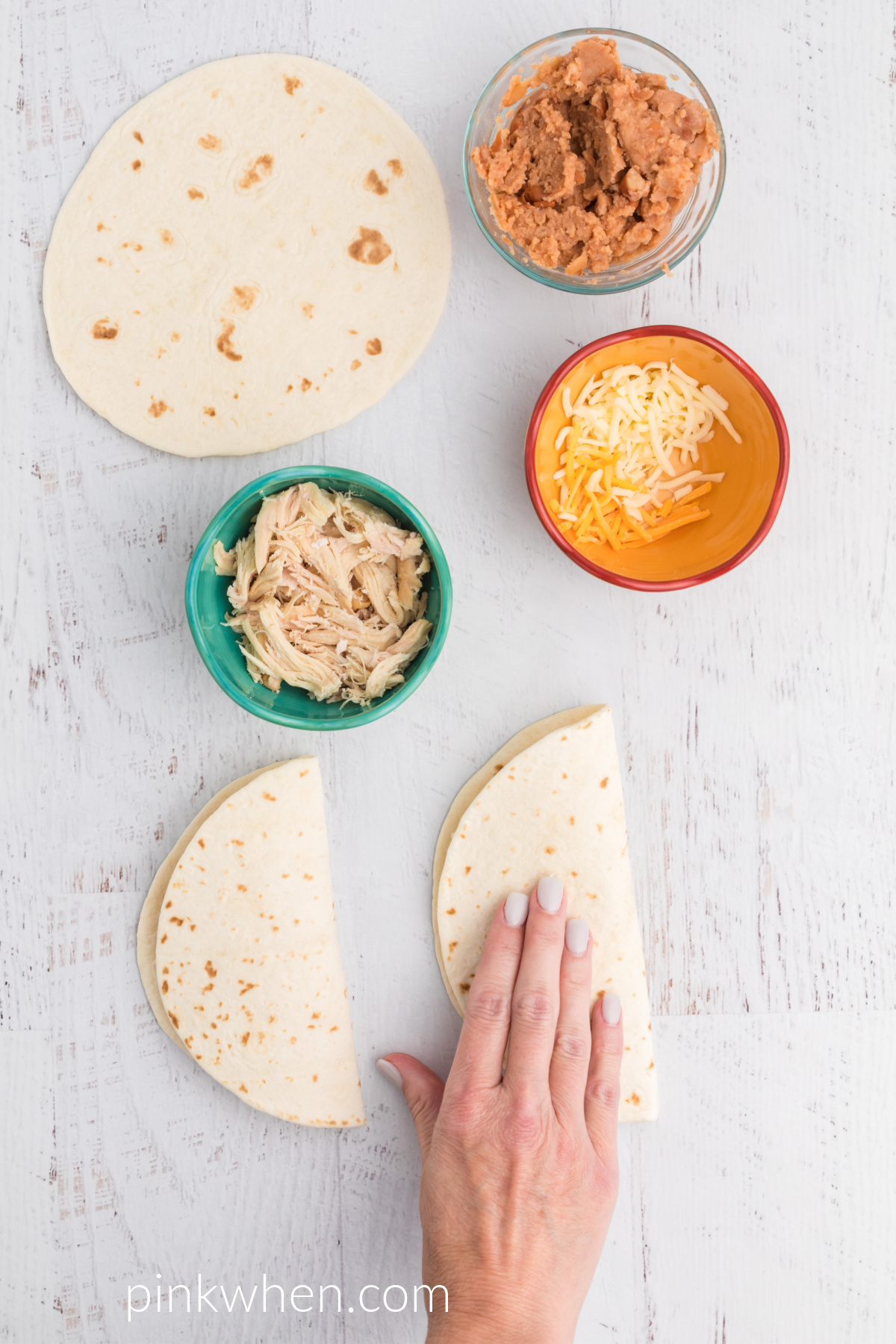 Hand folding over quesadillas before placing them into the air fryer.