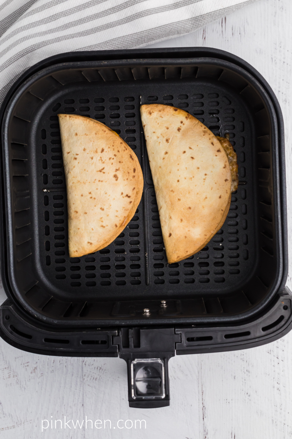Cooked quesadillas in the air fryer basket.
