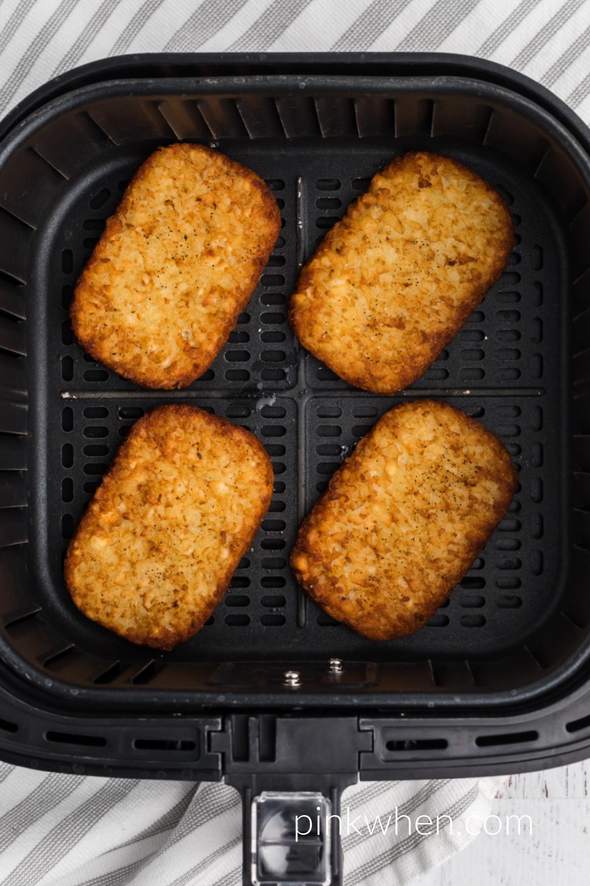 Crispy brown hash brown patties in the air fryer basket.