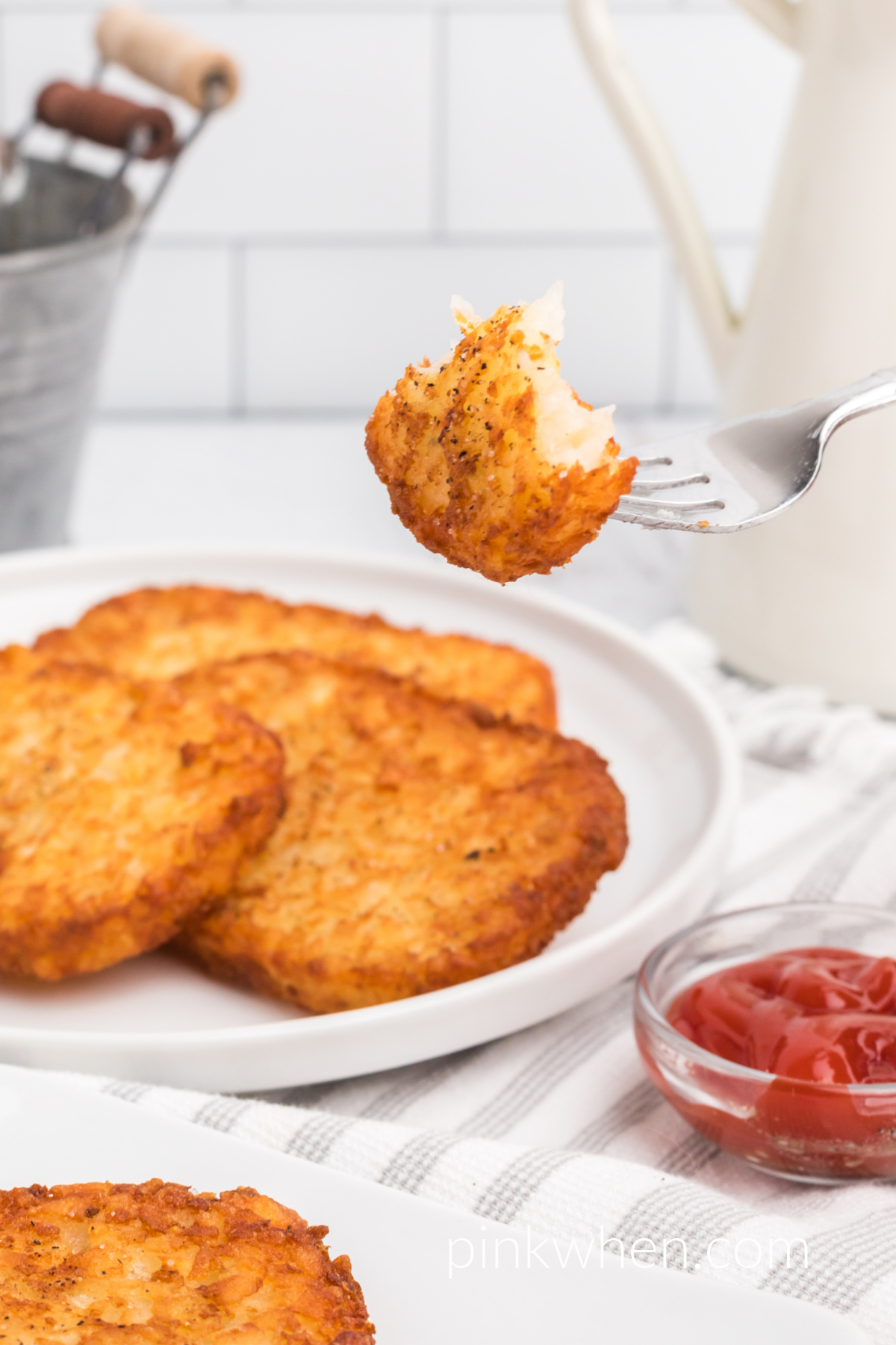Frozen Hash Brown Patties that were made in the air fryer, with a bite of has brown on a fork.