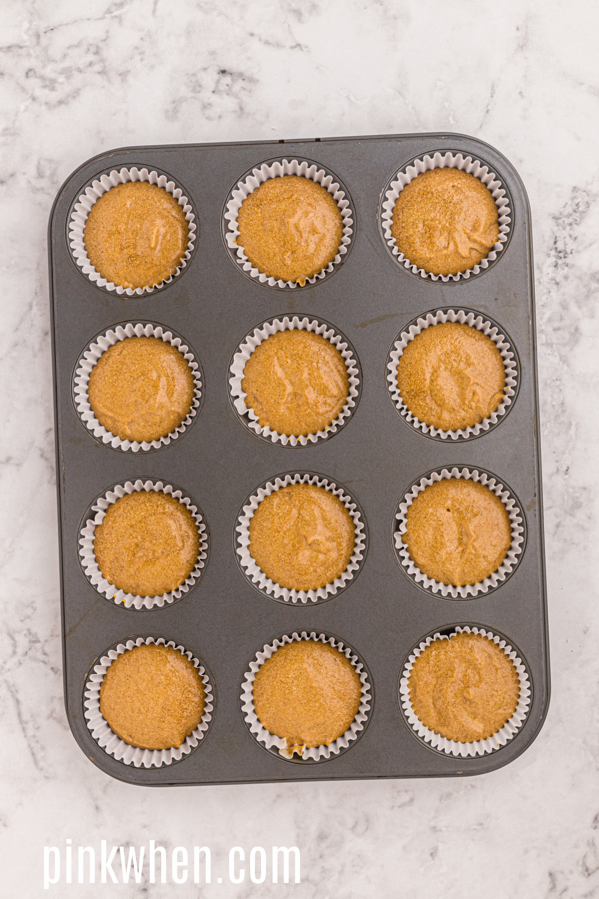 Gingerbread cupcakes in a cupcake tin ready to cool and then top with cream cheese frosting.