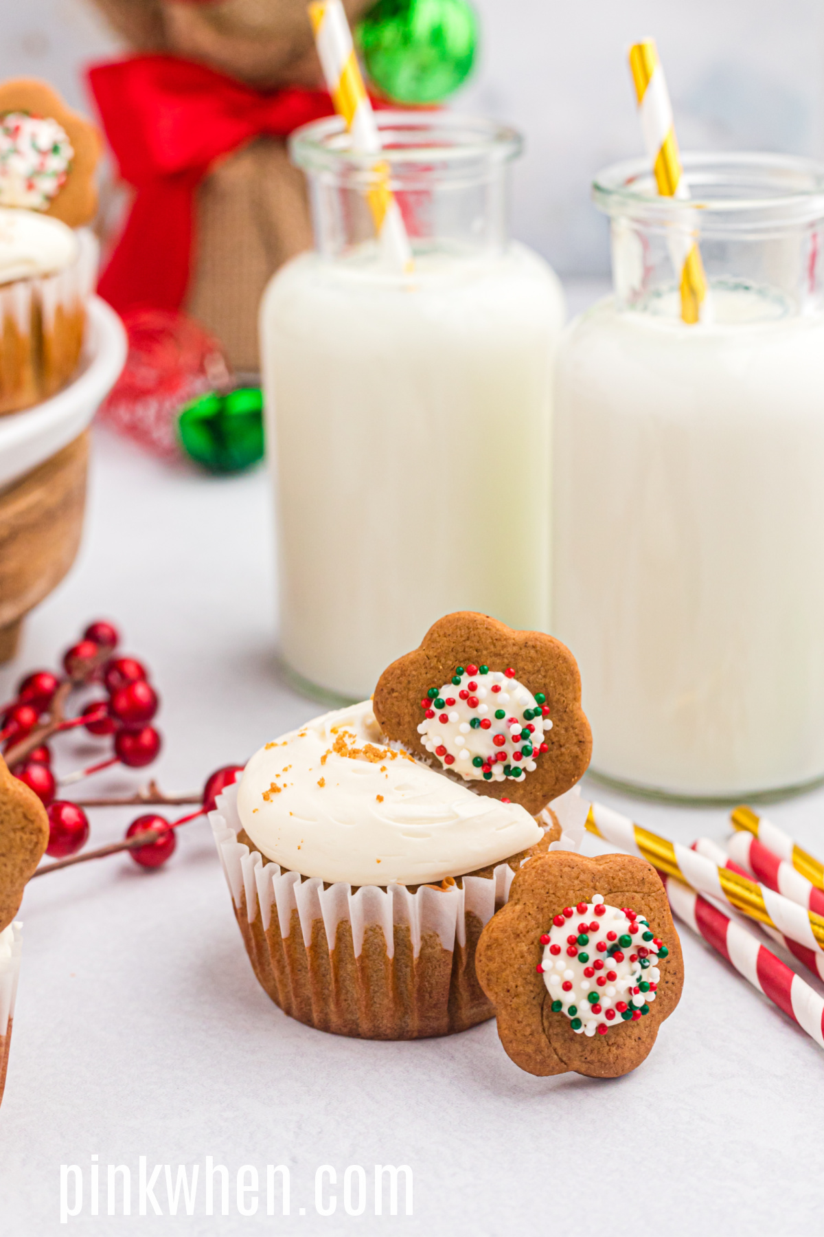 Gingerbread cupcake on a table with cookies and glasses of milk.