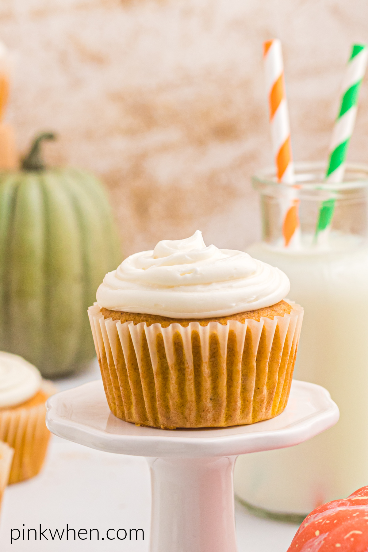 Pumpkin Spice Cupcake on a small pedestal ready to eat.