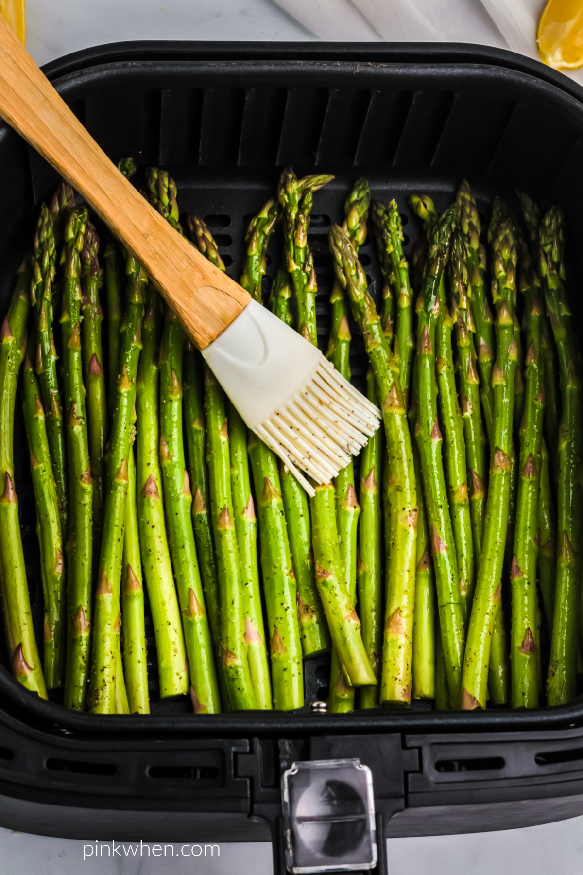 Asparagus in the air fryer basket being brushed with olive oil before air frying.
