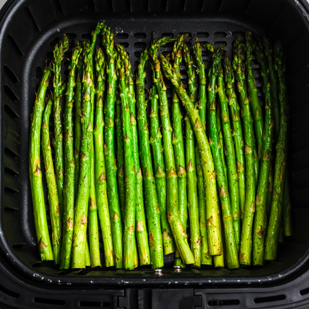 Air fried asparagus in the basket of the air fryer.
