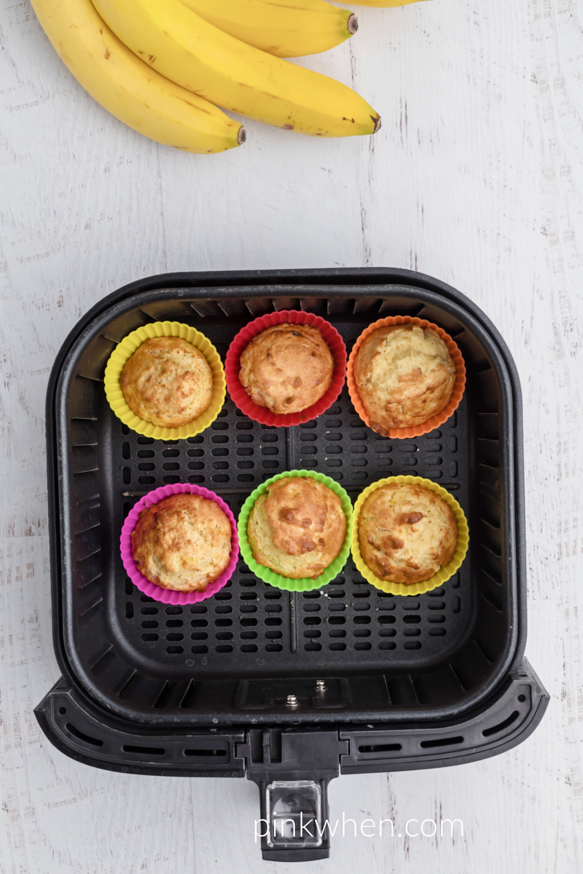 Baked banana muffins in the basket of the air fryer.
