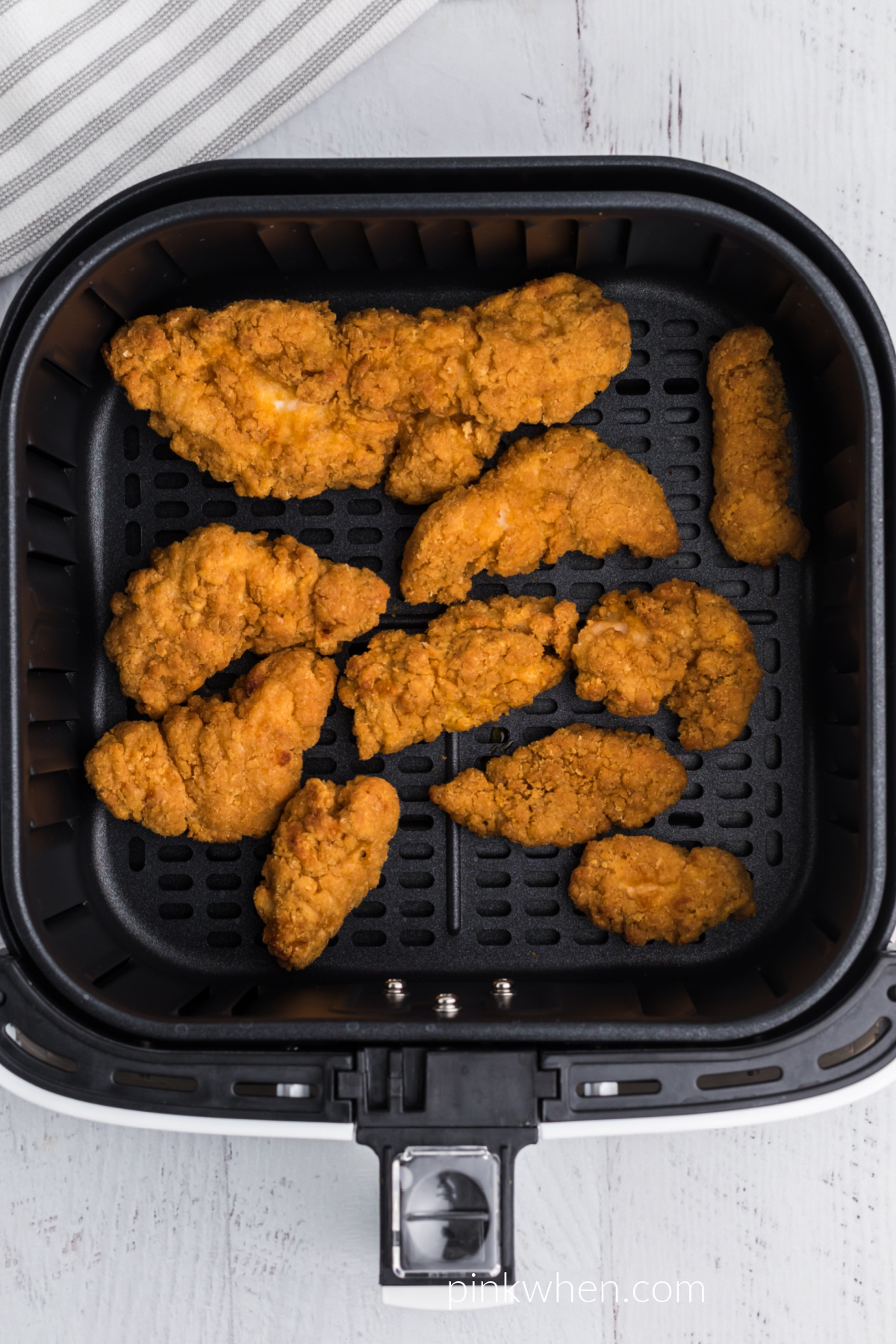 chicken strips fully cooked and in the basket of the air fryer, ready to serve.