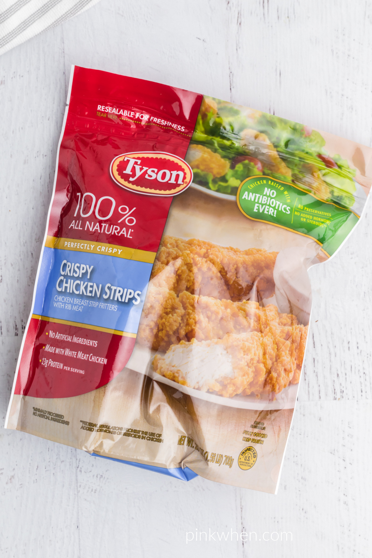 Package of Tyson frozen chicken strips on a white table.