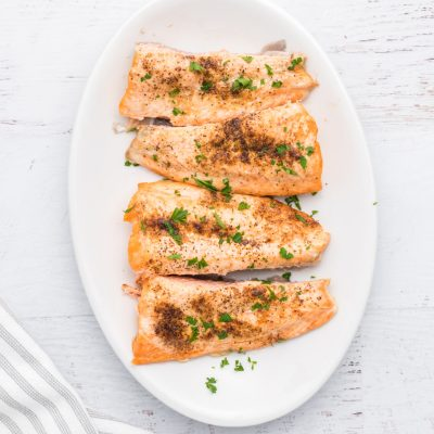 Salmon made in the air fryer on a white serving tray.