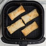 fully cooked frozen burritos in air fryer basket.